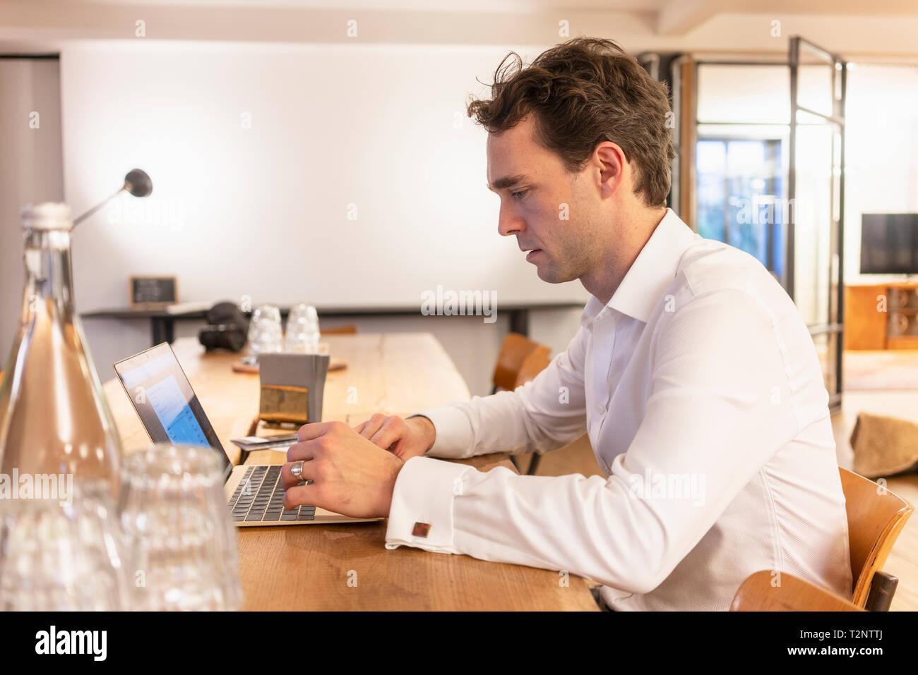Adulto medio imprenditore digitazione sul portatile in ufficio Immagini Stock