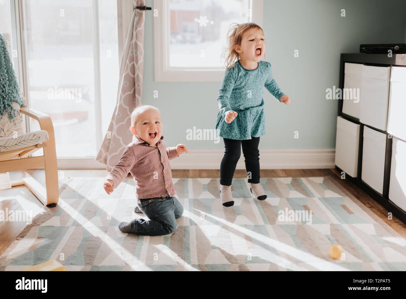 Femmina e toddler baby fratello giocando sul soggiorno rug Foto Stock