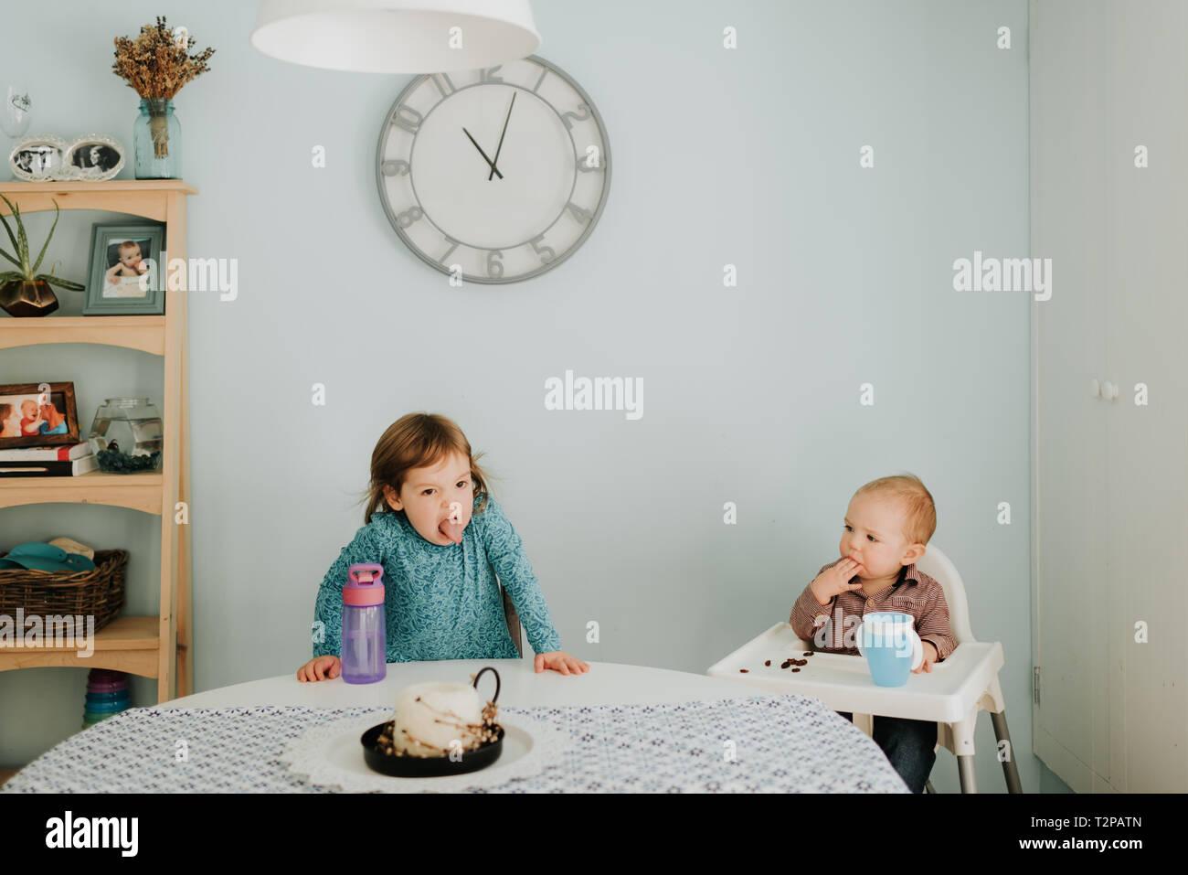 Toddler femmina a tavola e baby fratello in sedia alta Foto Stock