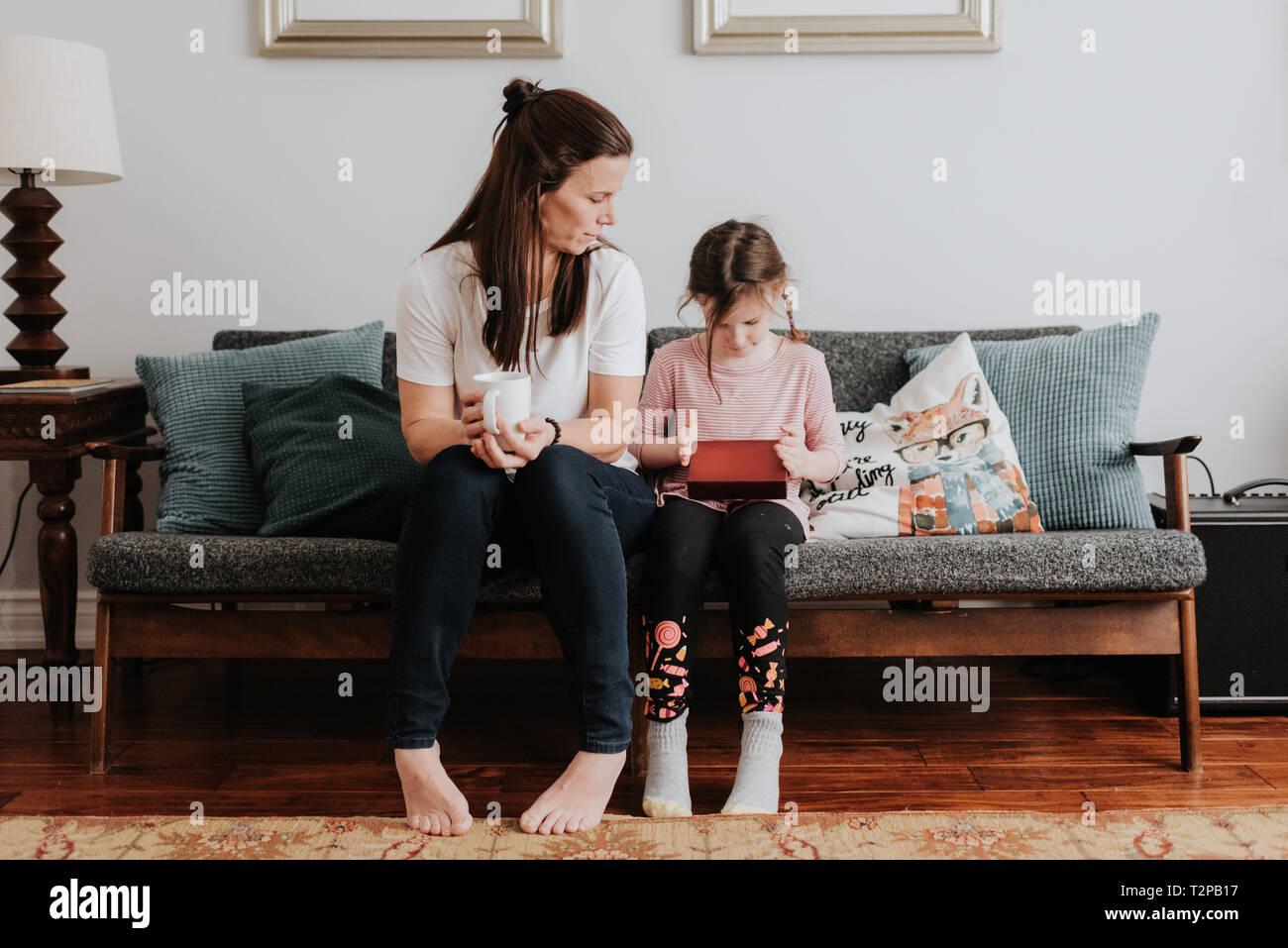 Madre guarda la figlia gioca sul lettino Foto Stock