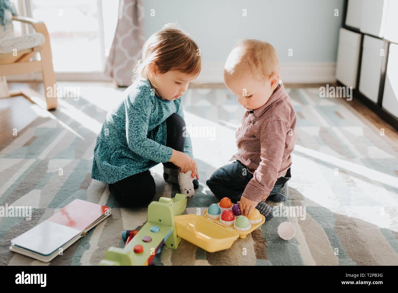 Toddler femmina giocando con il fratellino in salotto Foto Stock