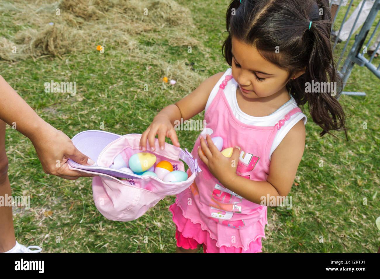Miami Florida Margaret Pace Park Pasqua Eggstravaganza evento familiare caccia all'uovo di tradizione vacanze uovo di plastica raccogliere ragazza ispanica Immagini Stock