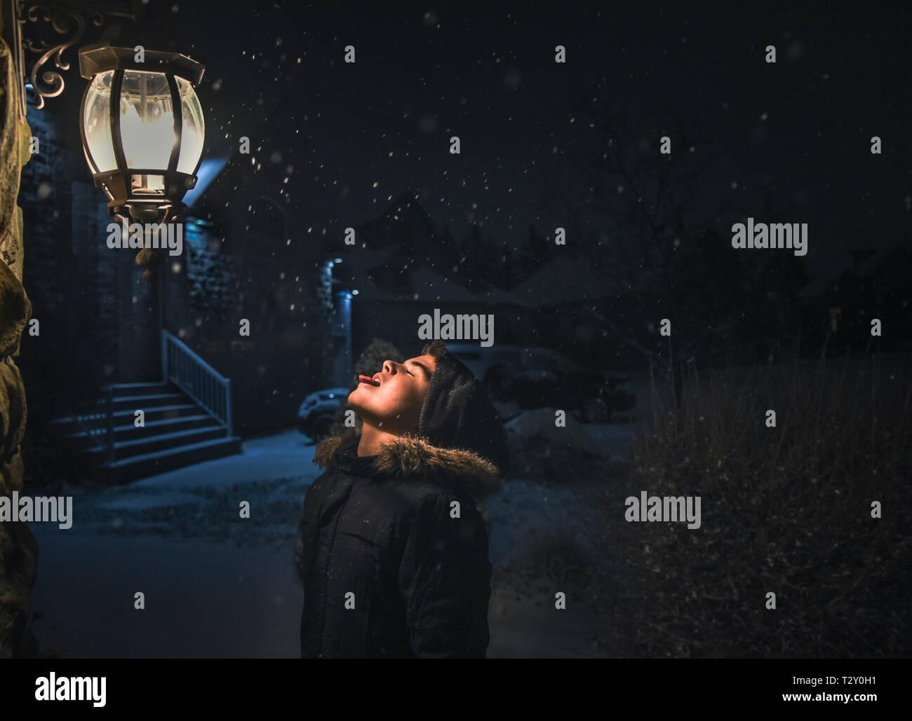 Ragazzo cattura i fiocchi di neve sulla sua linguetta accanto a una luce su una notte nevosa Foto Stock