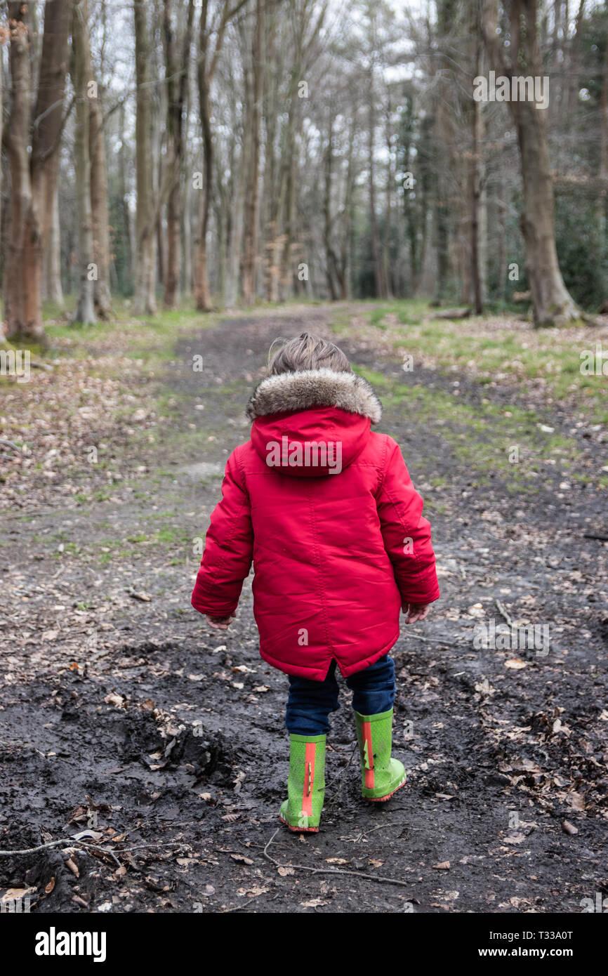 Piccolo Ragazzo in cappotto rosso e verde wellies