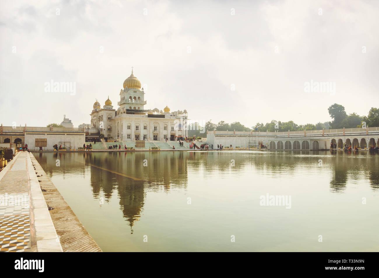Gurdwara Bangla Sahib è il più prominente Gurdwara Sikh. Un luogo sacro della religione sikhi. Cupola dorata del tempio di colore giallo brillante sun. Una lar Foto Stock