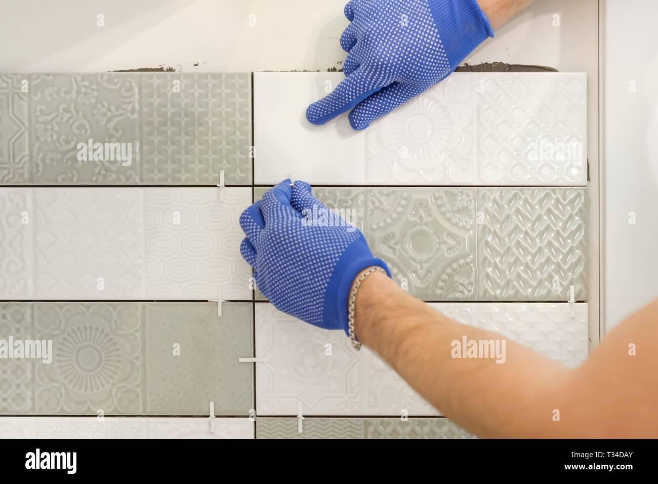Installazione di piastrelle in ceramica sulla parete in cucina