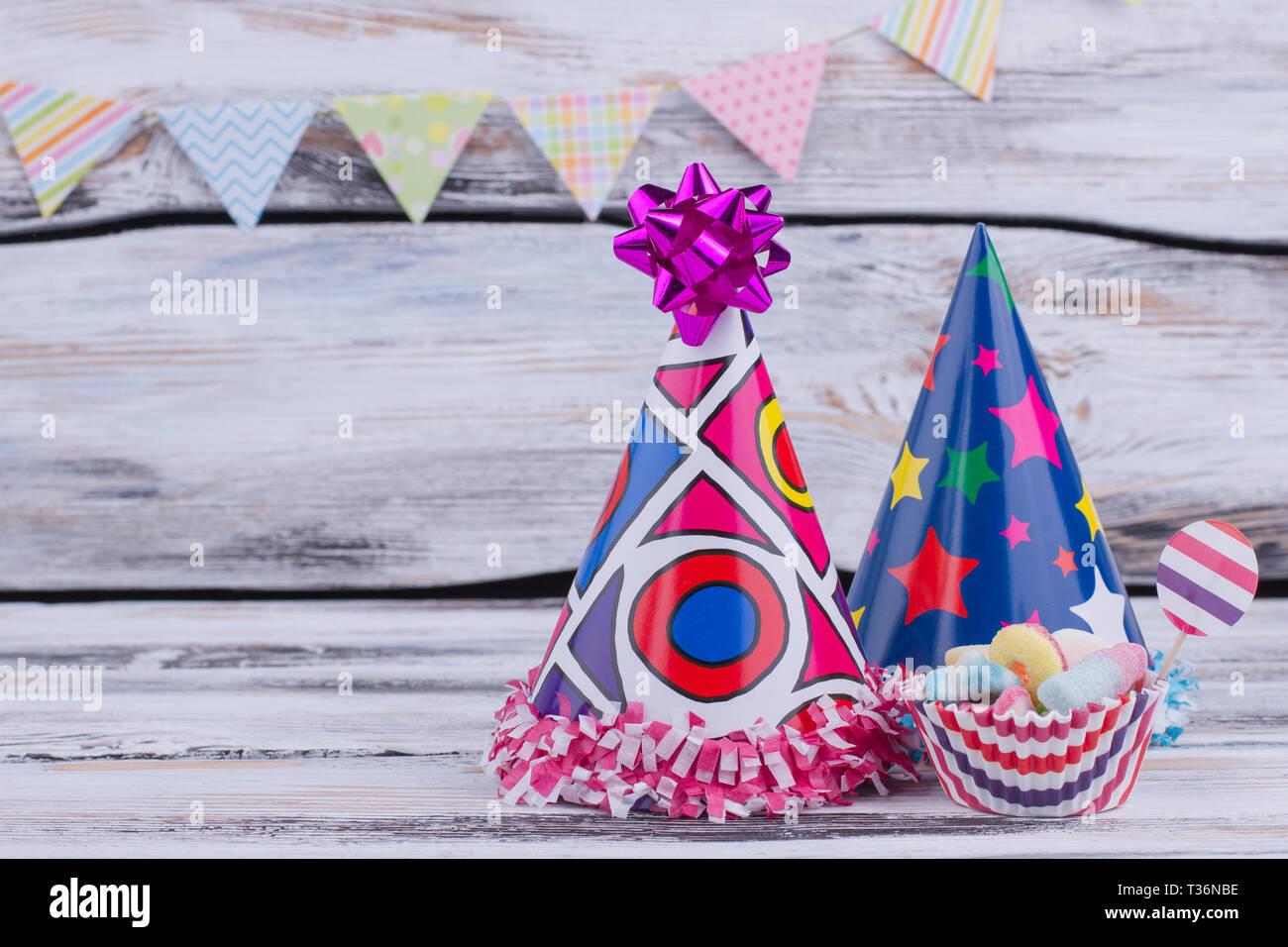 Il carnevale o la festa di compleanno di decorazioni. Decorate per i cappelli di carta e caramelle su sfondo di legno. Concetto di bambini festa di compleanno. Foto Stock