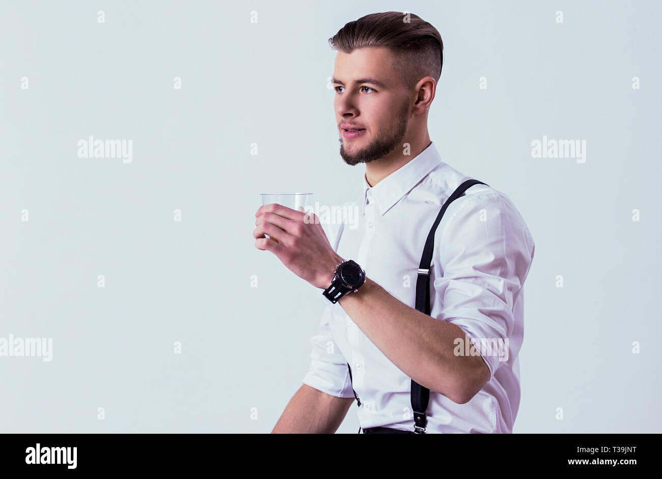 f4e7dd4482906f Ritratto di uomo elegante in usura classica di bere whisky o scotch mentre  in piedi contro uno sfondo grigio. Fiducioso Uomo in camicia bianca e  sospesa