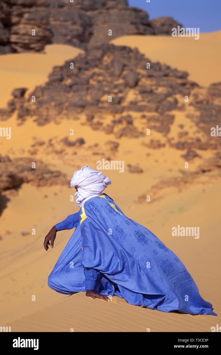 Touareg seduto su una duna nel deserto del Sahara, Algeria Immagini Stock