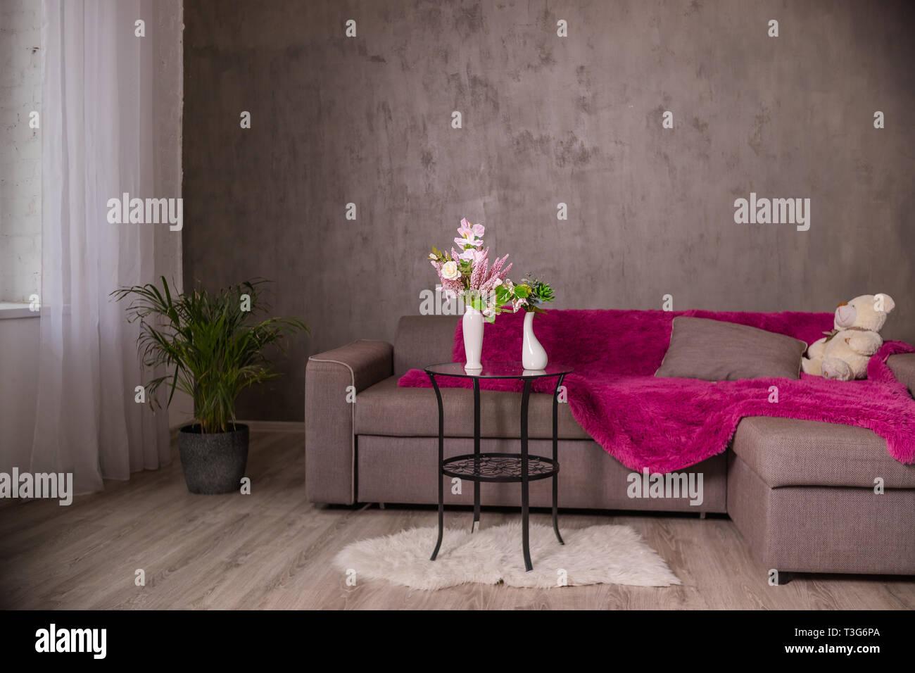 Scandinavian Living room design interno con divano e tavolo tondo con bouquet di fiori.Braun divano con plaid, cuscini, Teddy bear.arredamento moderno Foto Stock
