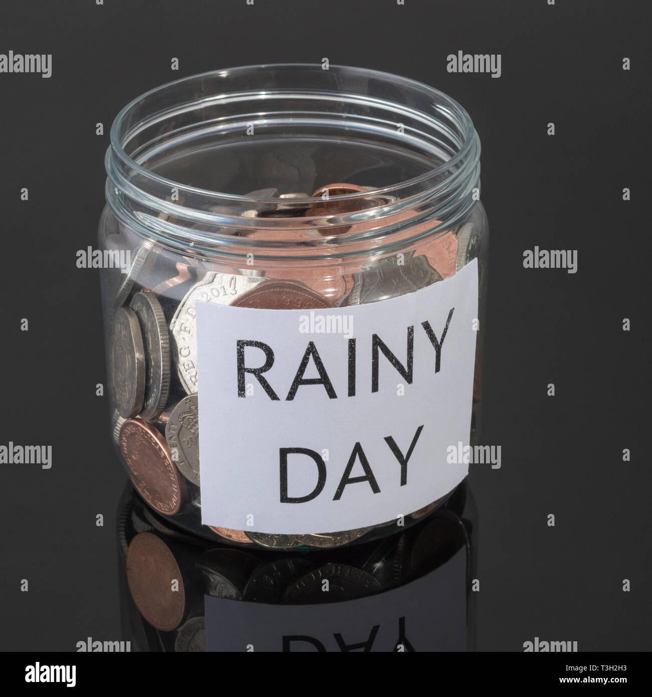 Contenitore di plastica contenente le monete del Regno Unito. Metafora risparmi personali, Rainy day risparmio, risparmi pensionistici pot, Risparmi pensione, il risparmio per il pensionamento . Foto Stock