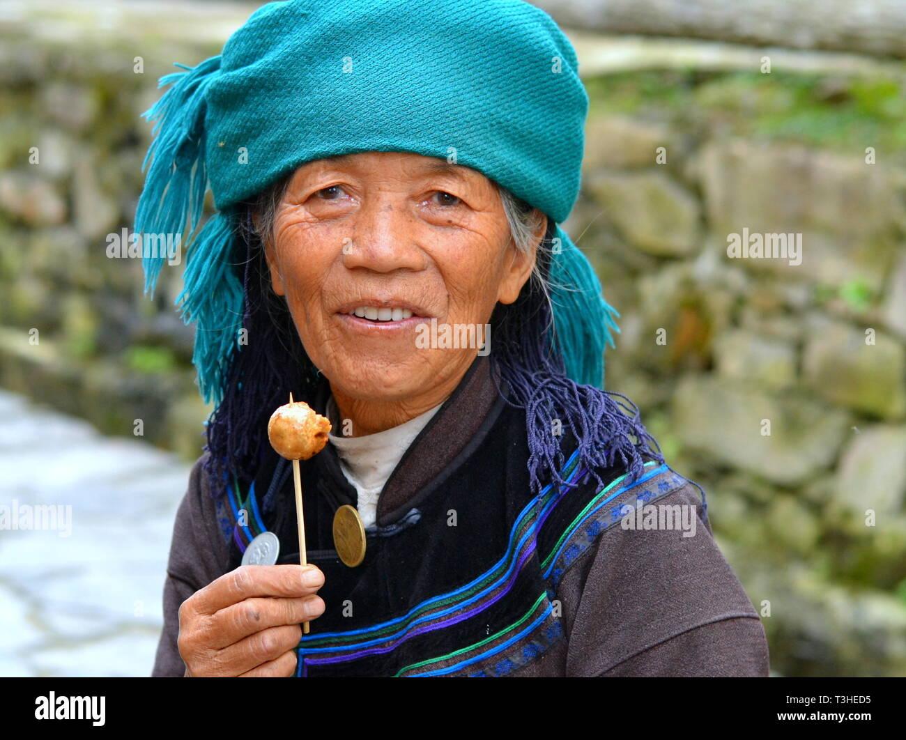 Anziani Hani donna (Cinese minoranza etnica) indossa un nero e blu abito tradizionale con un color turchese velo e mangia tofu fritto. Immagini Stock
