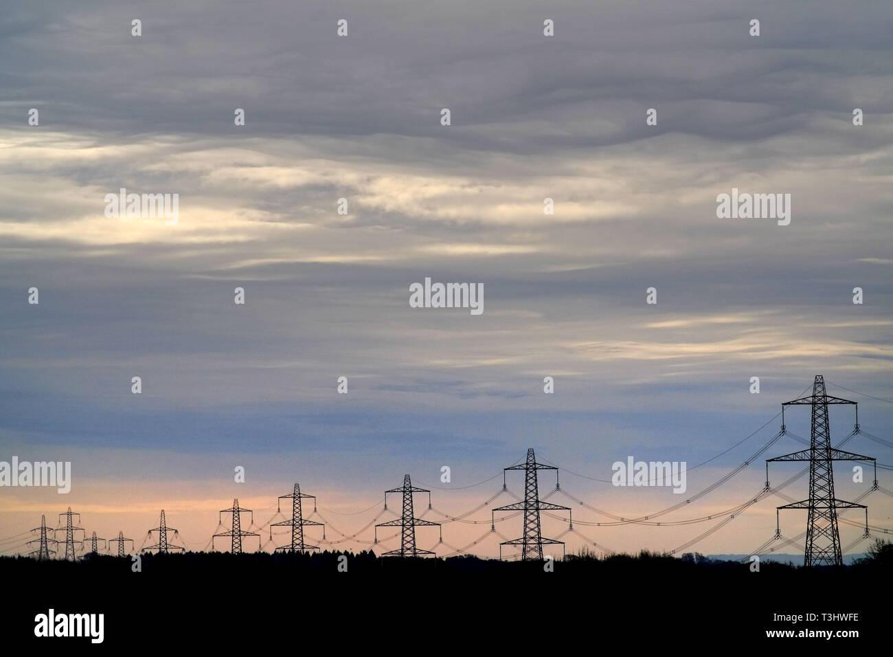 Le linee di alimentazione / elettricità piloni sotto un cielo turbolento Immagini Stock