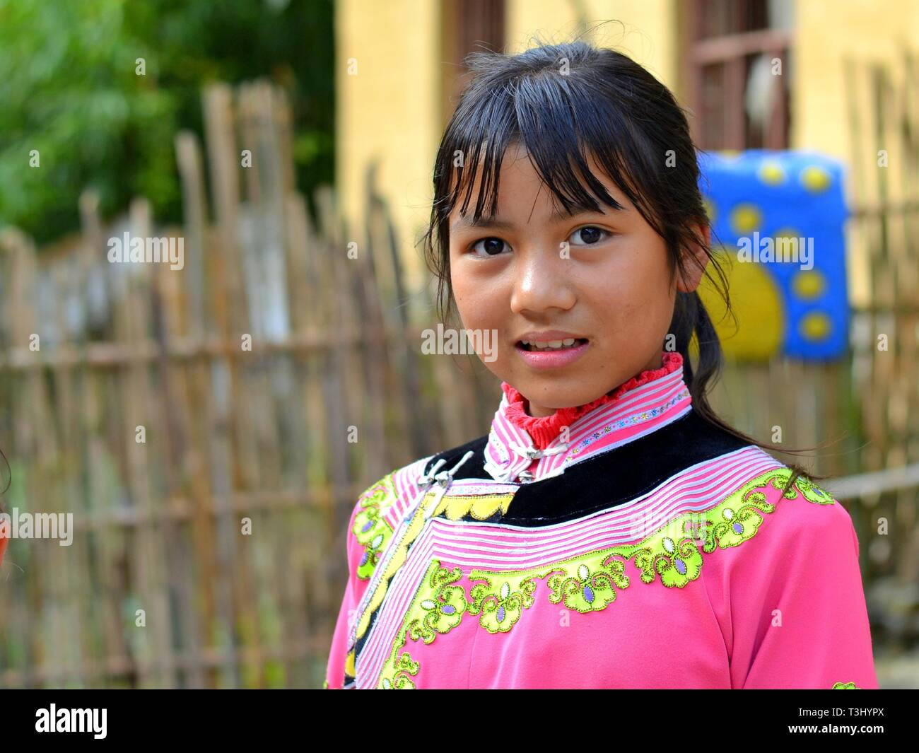 Bella ragazza Miao (Cinese minoranza etnica) indossa una rosa tradizionale etnica costume e pone per la fotocamera. Immagini Stock