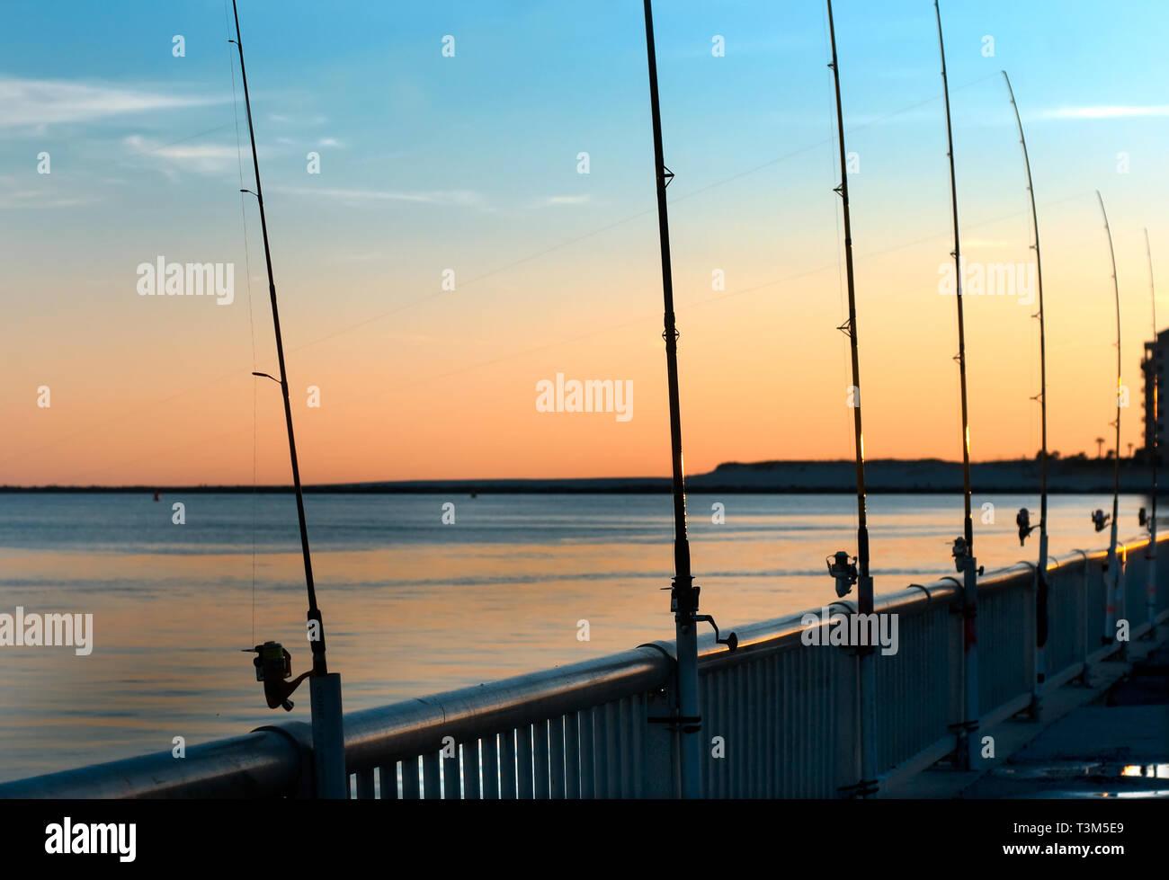 Poli di pesca rimangono inattivi come il sole tramonta a Florida punto pier, nov. 12, 2009, in Orange Beach, Alabama. Foto Stock