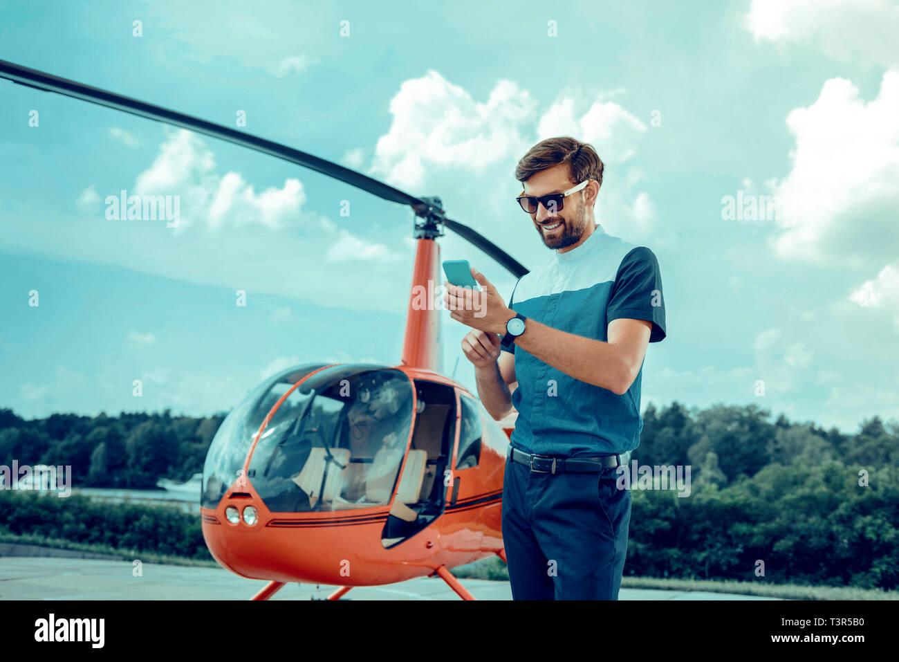 Sorridente buon-cerca uomo in occhiali da sole il controllo sociale dei media Immagini Stock