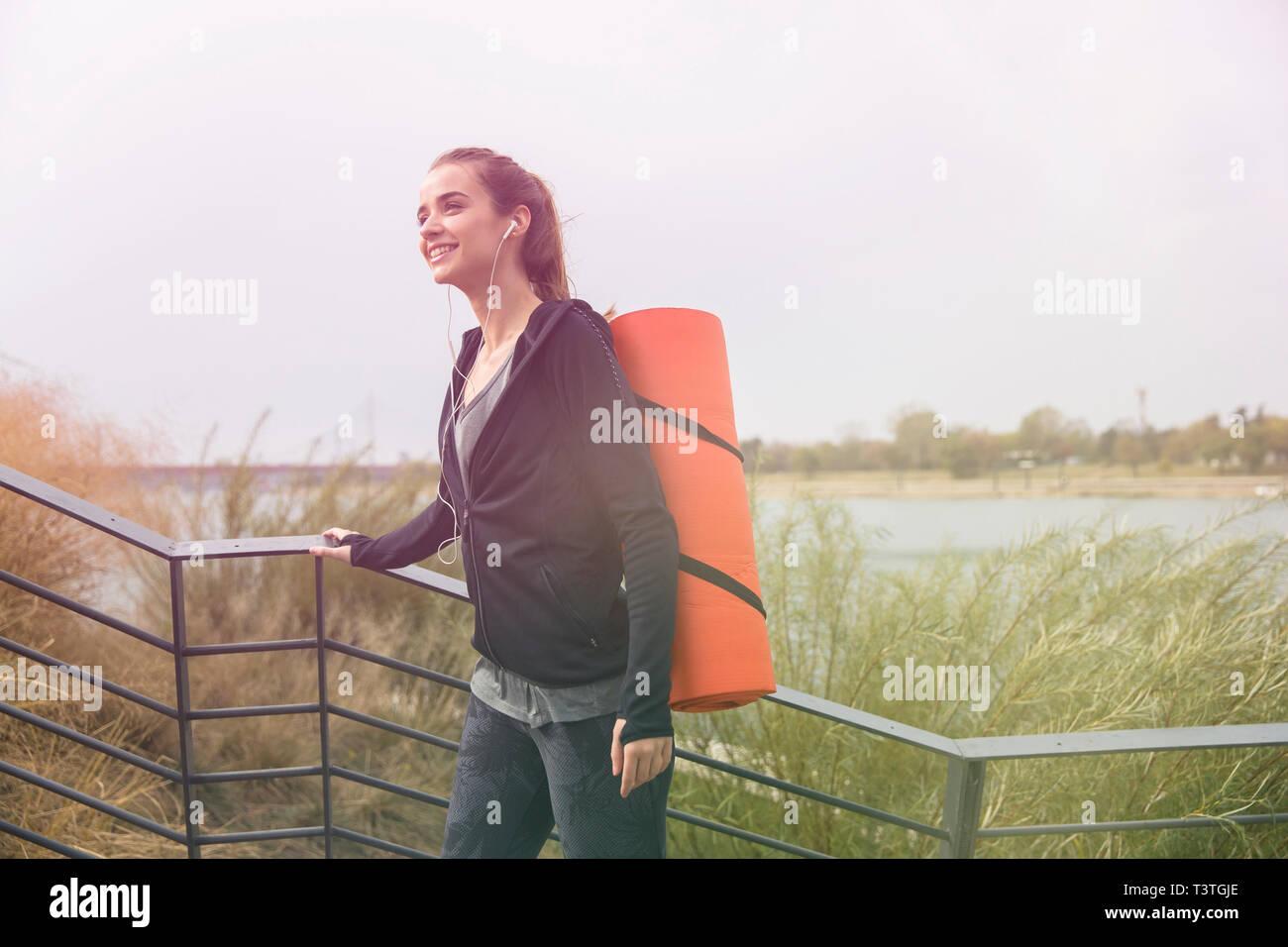 Giovane donna fitness walking con mat sul retro per esterno Foto Stock