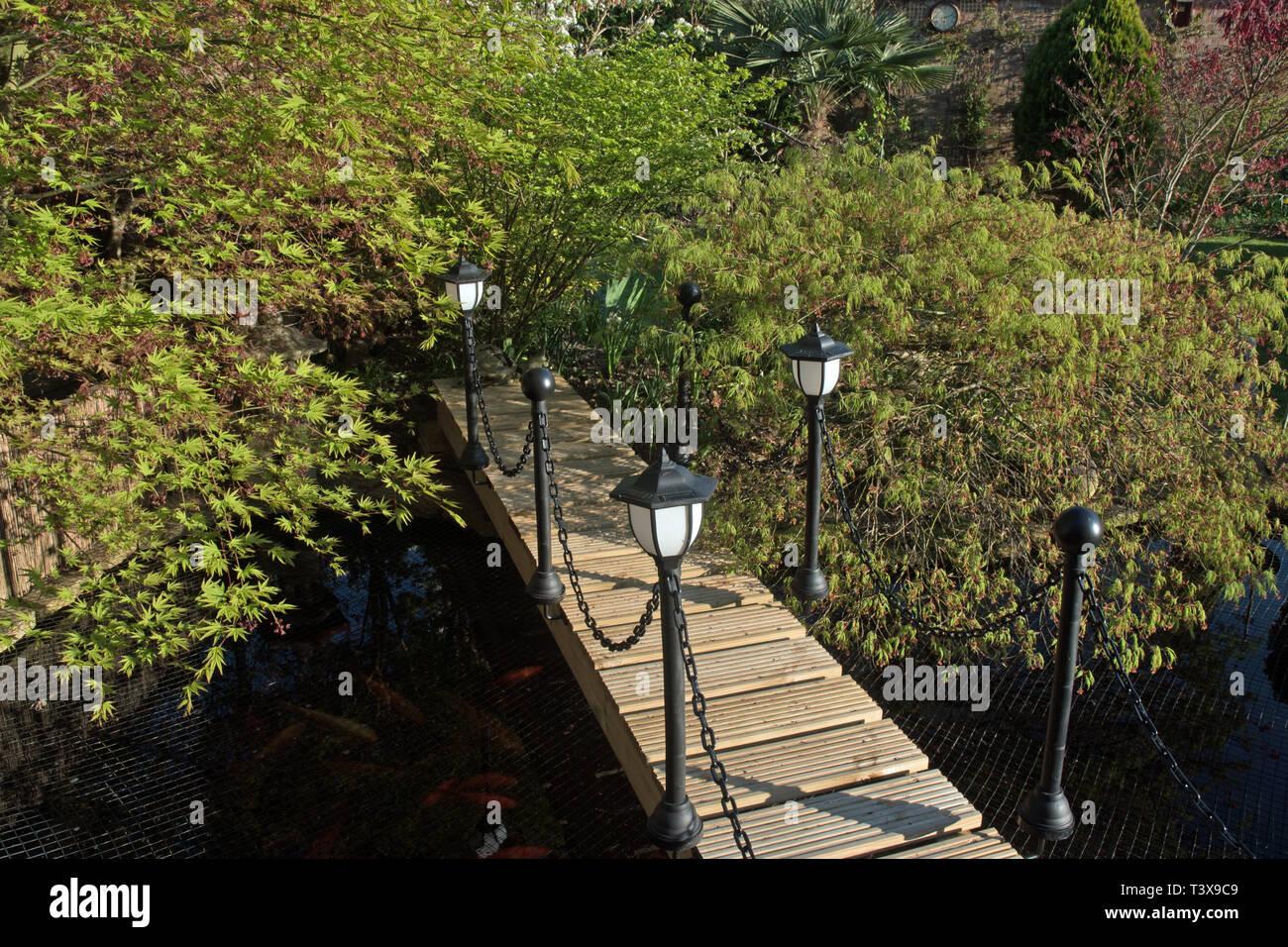 Poco costoso passerella in legno con illuminazione solare su stagno