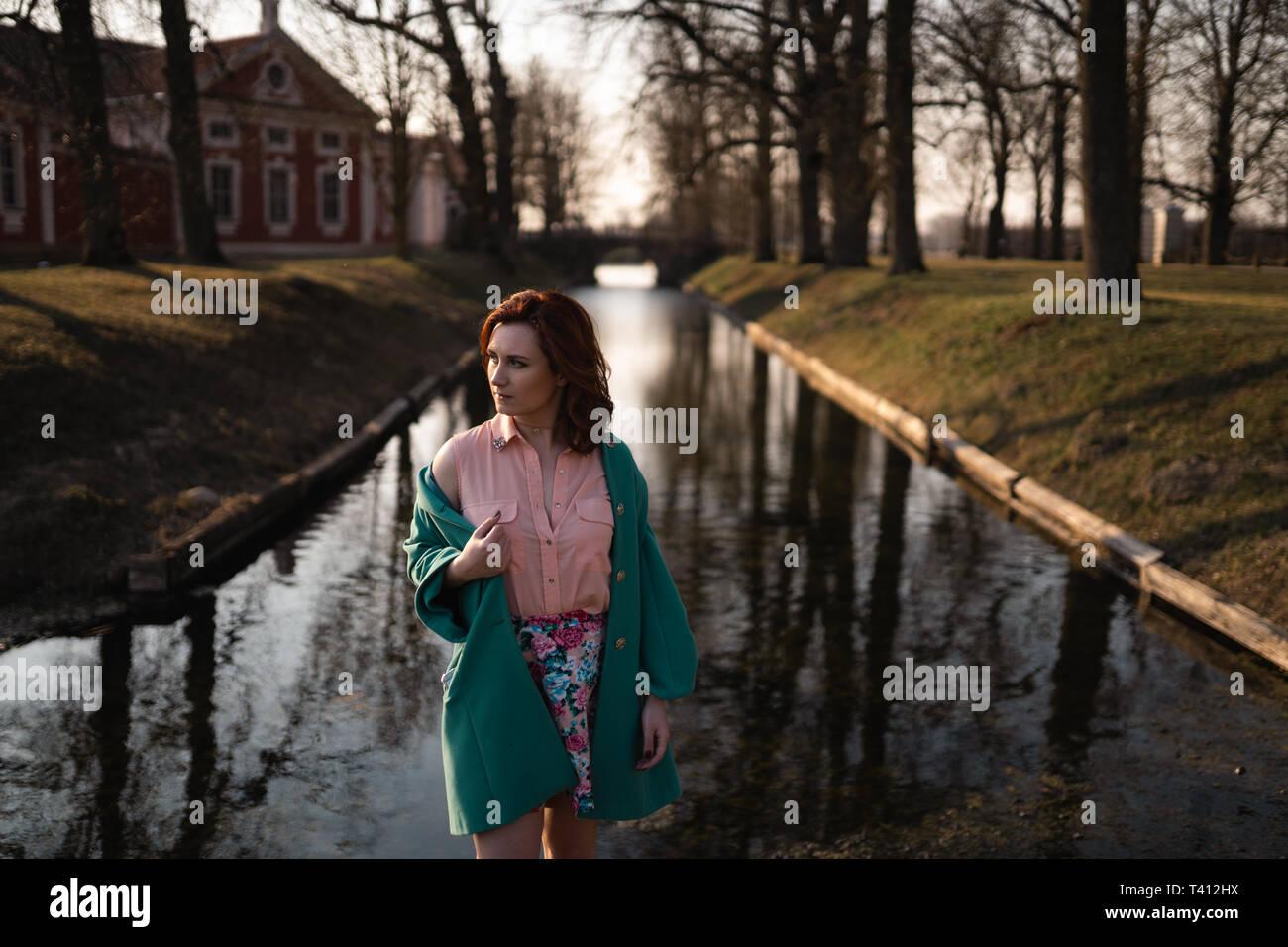 Bella giovane donna rilassante vicino a un fiume di canale in un parco vicino al Palazzo di Rundale, Lettonia, 2019 Foto Stock