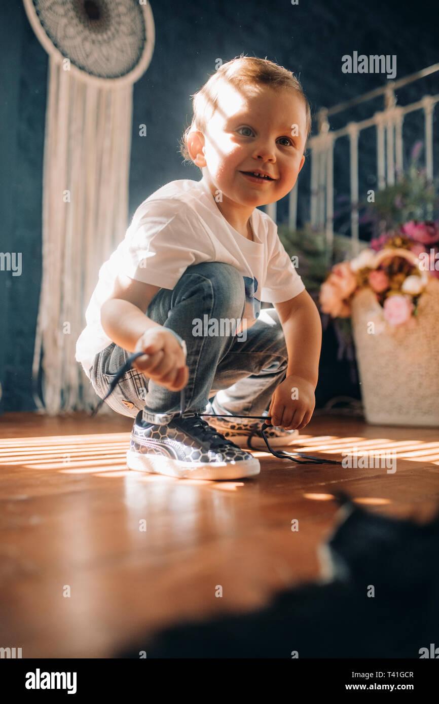 Il Toddler boy impara a legare i lacci delle scarpe sul suo sneakers opposto della finestra. Foto Stock