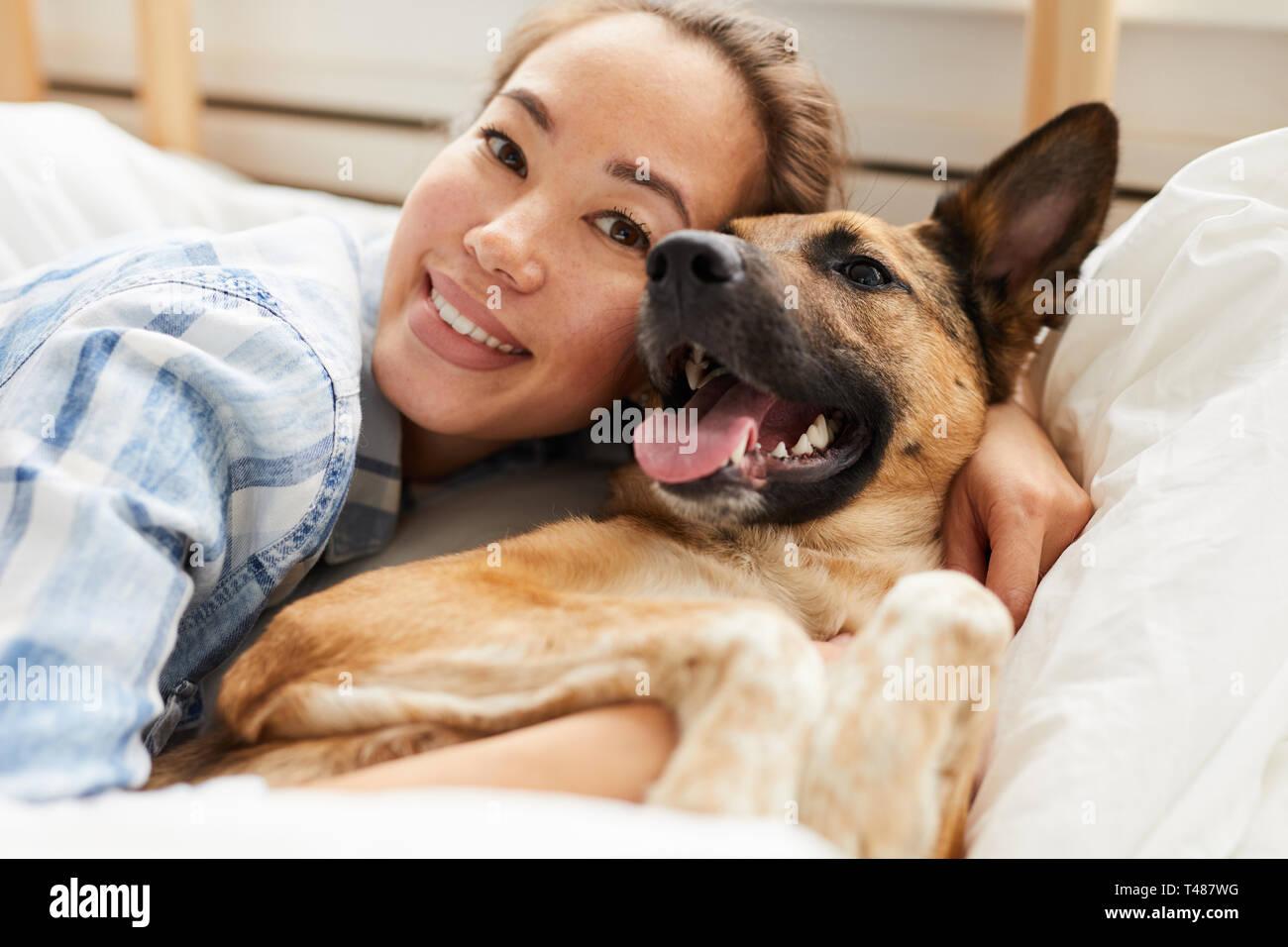 Bella donna asiatica abbracciando il cane Foto Stock
