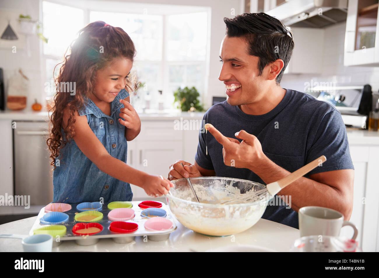 Giovane ragazza sta al tavolo della cucina a fare torte con suo padre, assaggiando il cake mix, close up Foto Stock