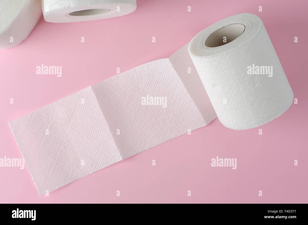 Singola bianco carta igienica rotolo sul rosa pastello sfondo. Spazio per il testo. Uso quotidiano oggetto. Scopo igienico Immagini Stock