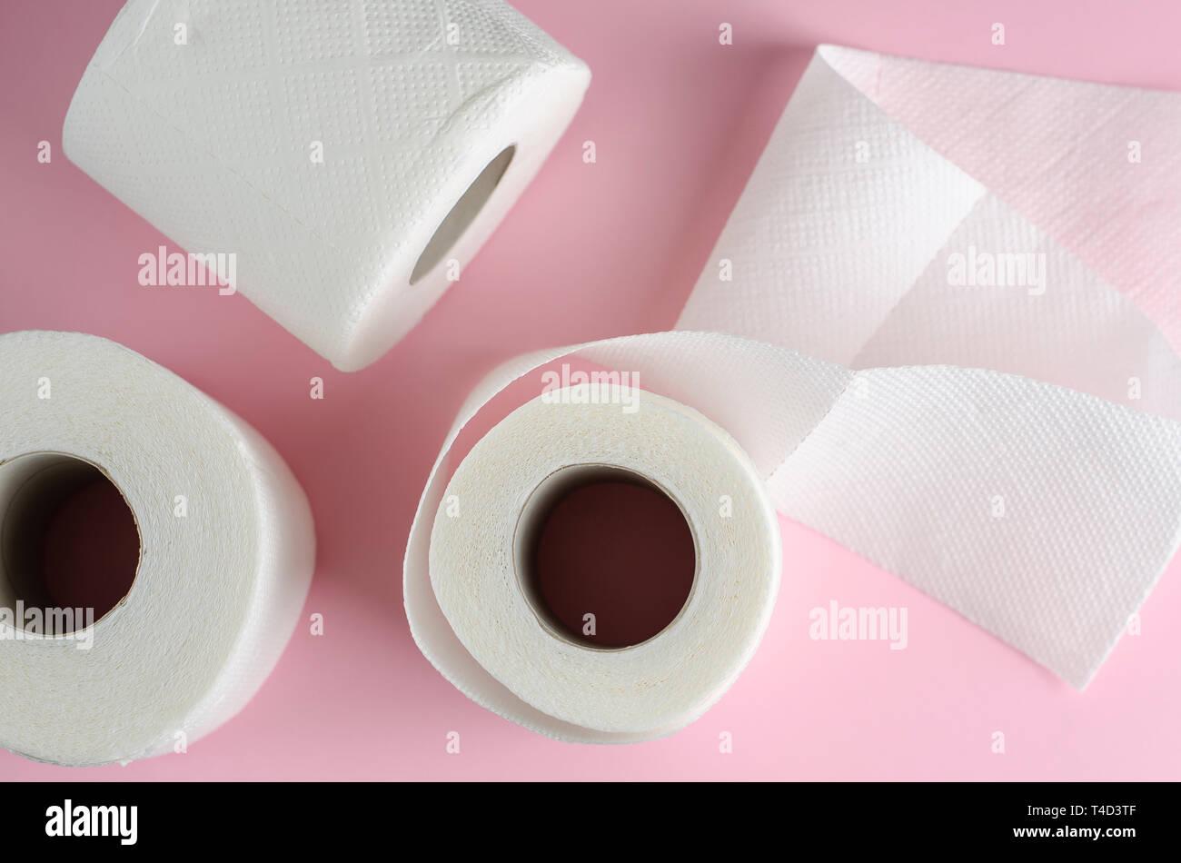 White rotoli di carta igienica pastello su sfondo rosa. Spazio per il testo. Igienici e di uso quotidiano oggetto. Immagini Stock