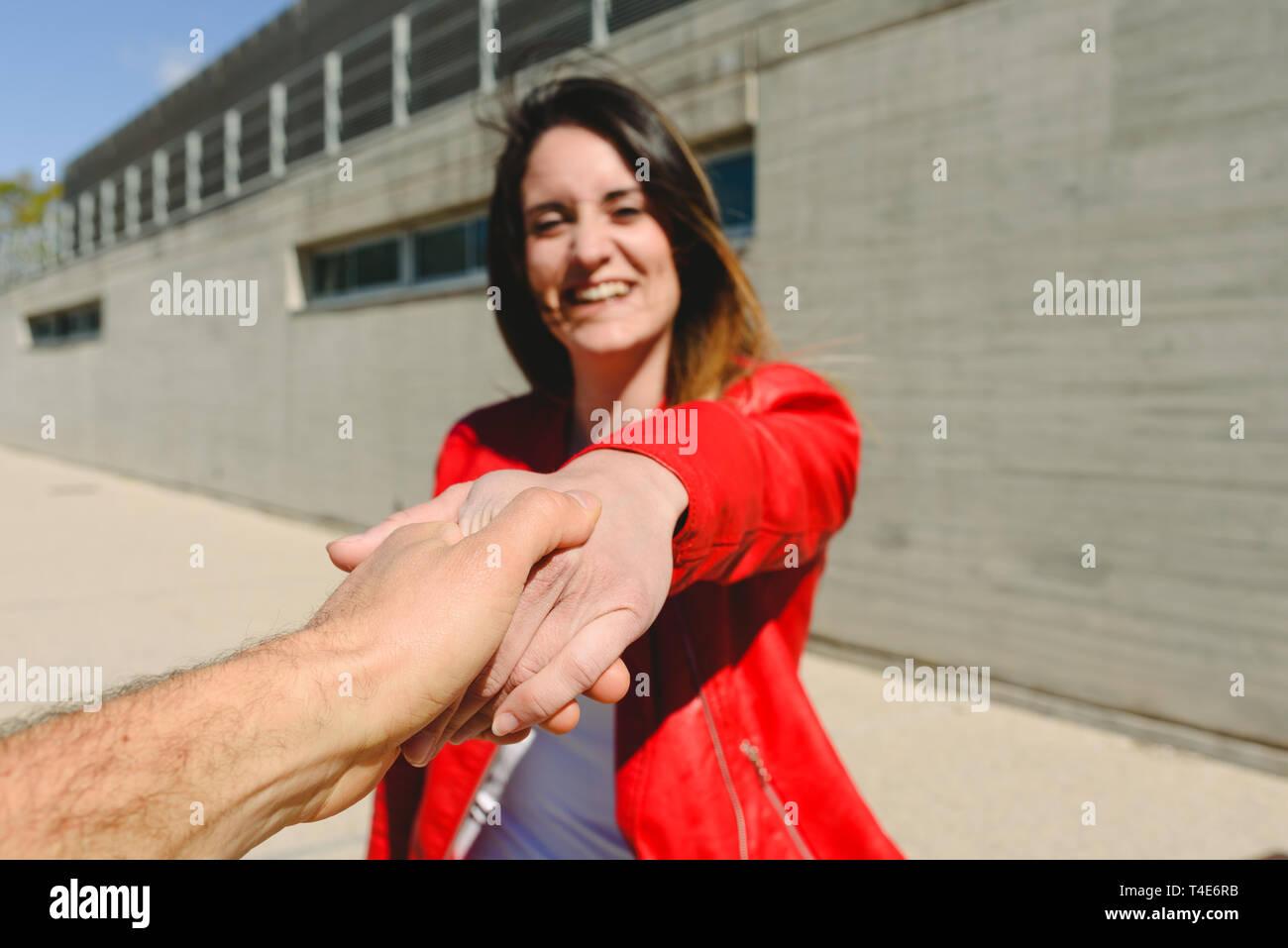 Giovane donna in giacca rossa tenendo la mano con il suo fidanzato sorridente. Immagini Stock