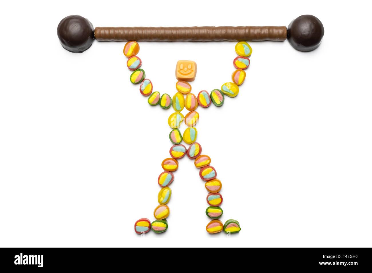 Vantaggi di dolcezza concetto, isolata. Piccolo uomo realizzato da caramelle con candy bar. Caramelle di dare forza e gioia. Carboidrati la vostra principale fonte di energ Immagini Stock