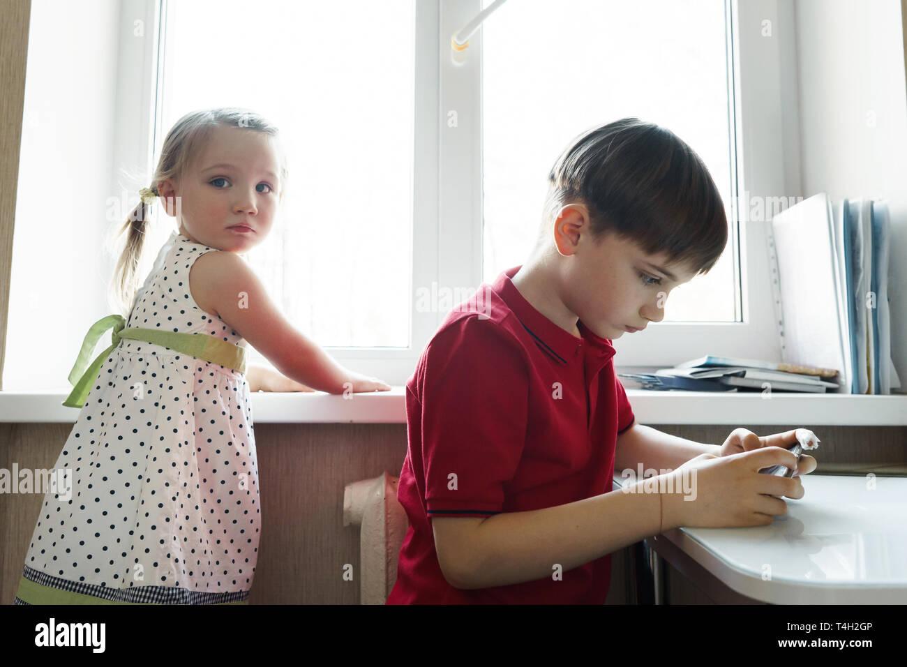 Sorella e fratello sono seduti in cucina e giocare con il telefono Foto Stock