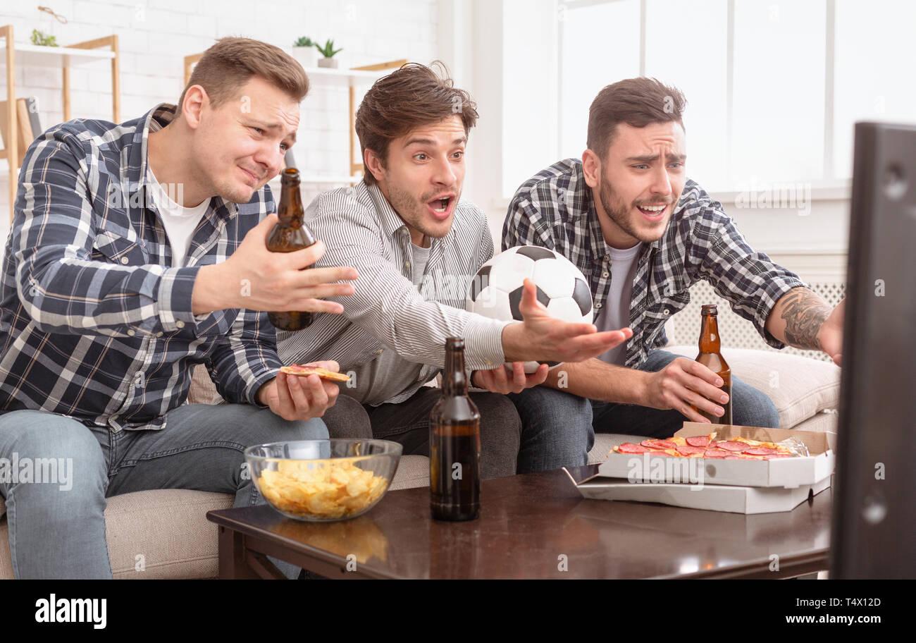 Delusi amici guardare la partita di football, arrabbiato per la perdita Immagini Stock