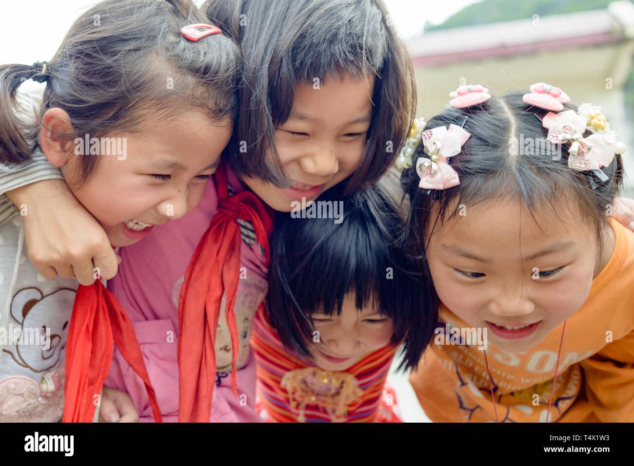 Quattro età primaria scuola ragazze nel gruppo abbraccio, ridendo e gridando. Regione di Guangxi, centrale Cina meridionale. Immagini Stock