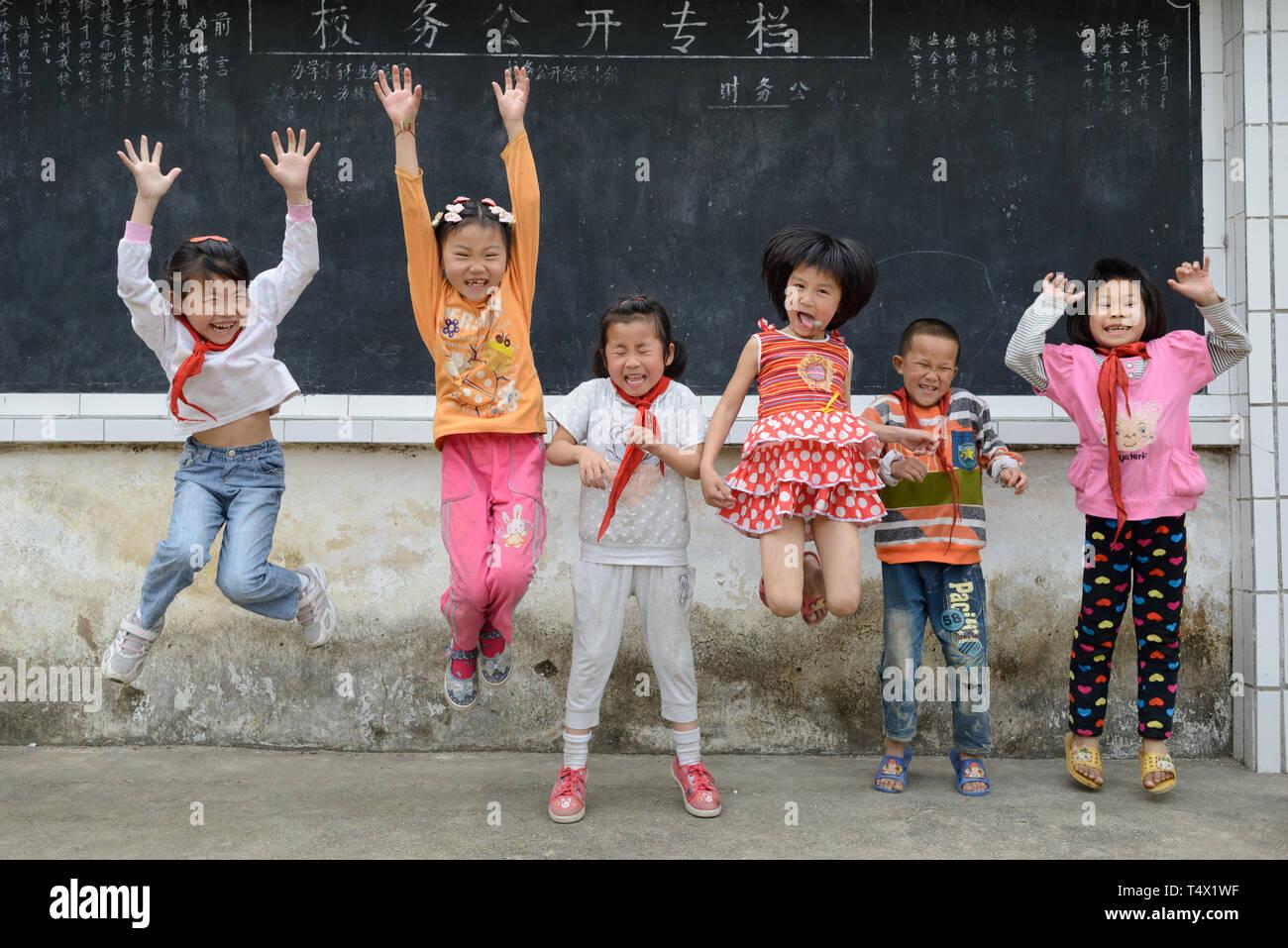 Età primaria scuola bambini saltando e ridendo nel parco giochi scuola rurale nella regione di Guangxi, centrale Cina meridionale. Immagini Stock