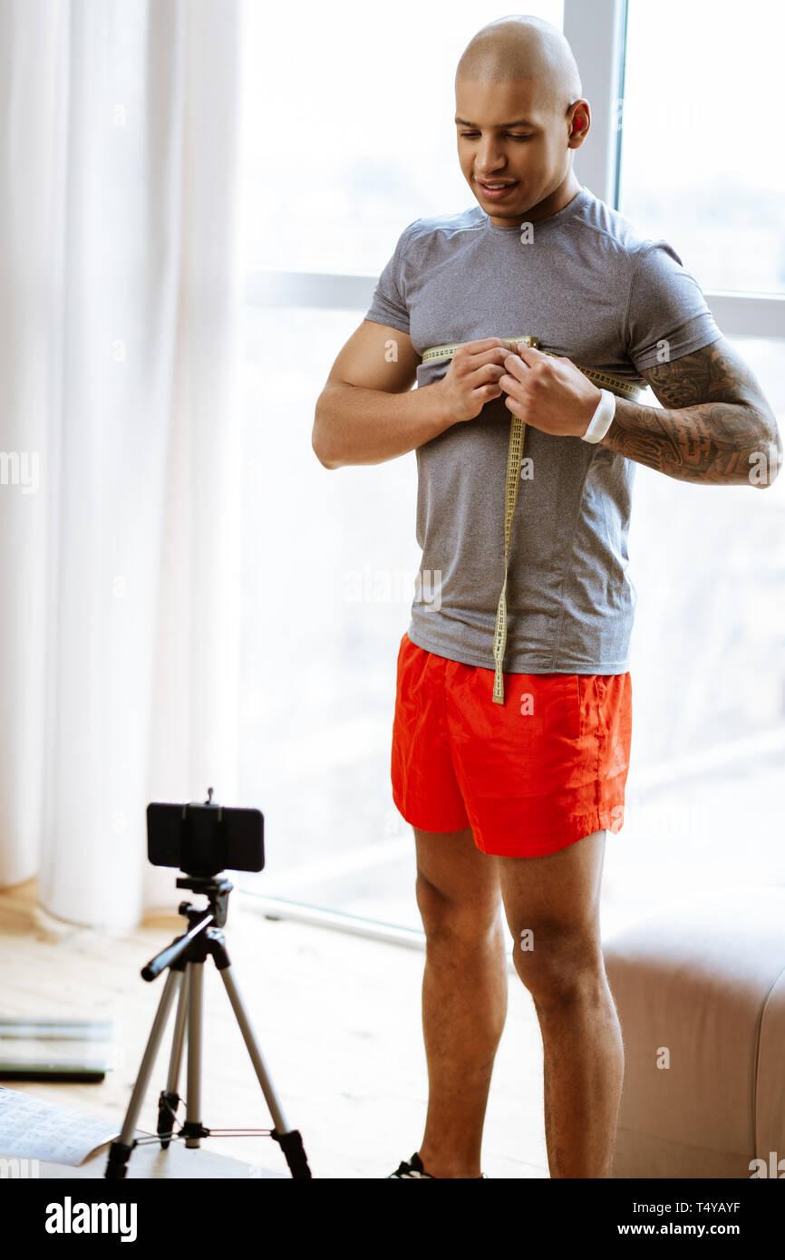 Atleta misurando il suo petto mentre le riprese video sul bodybuilding Immagini Stock