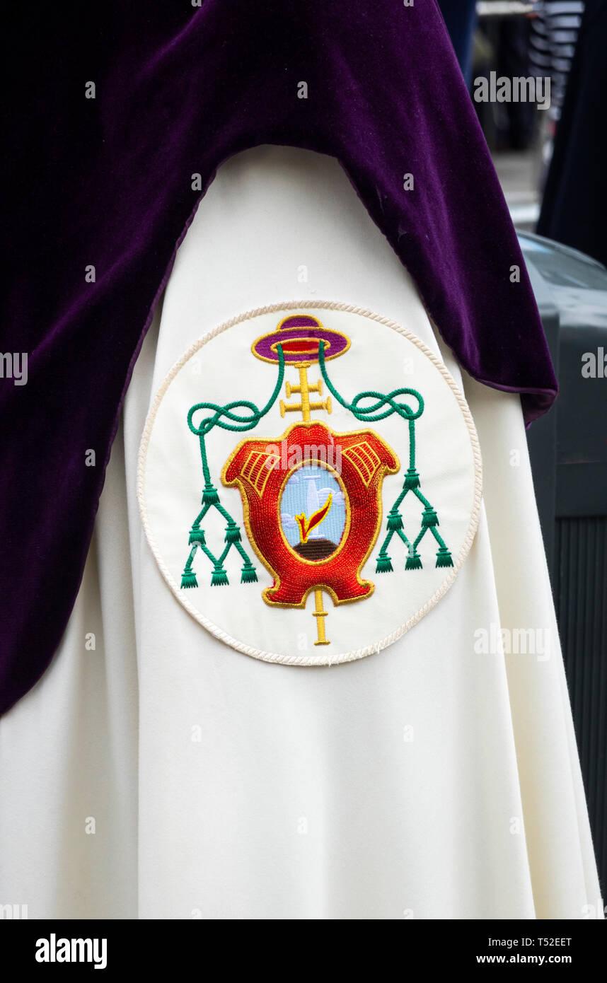 Fascia da braccio e viola il cofano per mostrare la fraternità in una settimana santa parade di Siviglia Immagini Stock