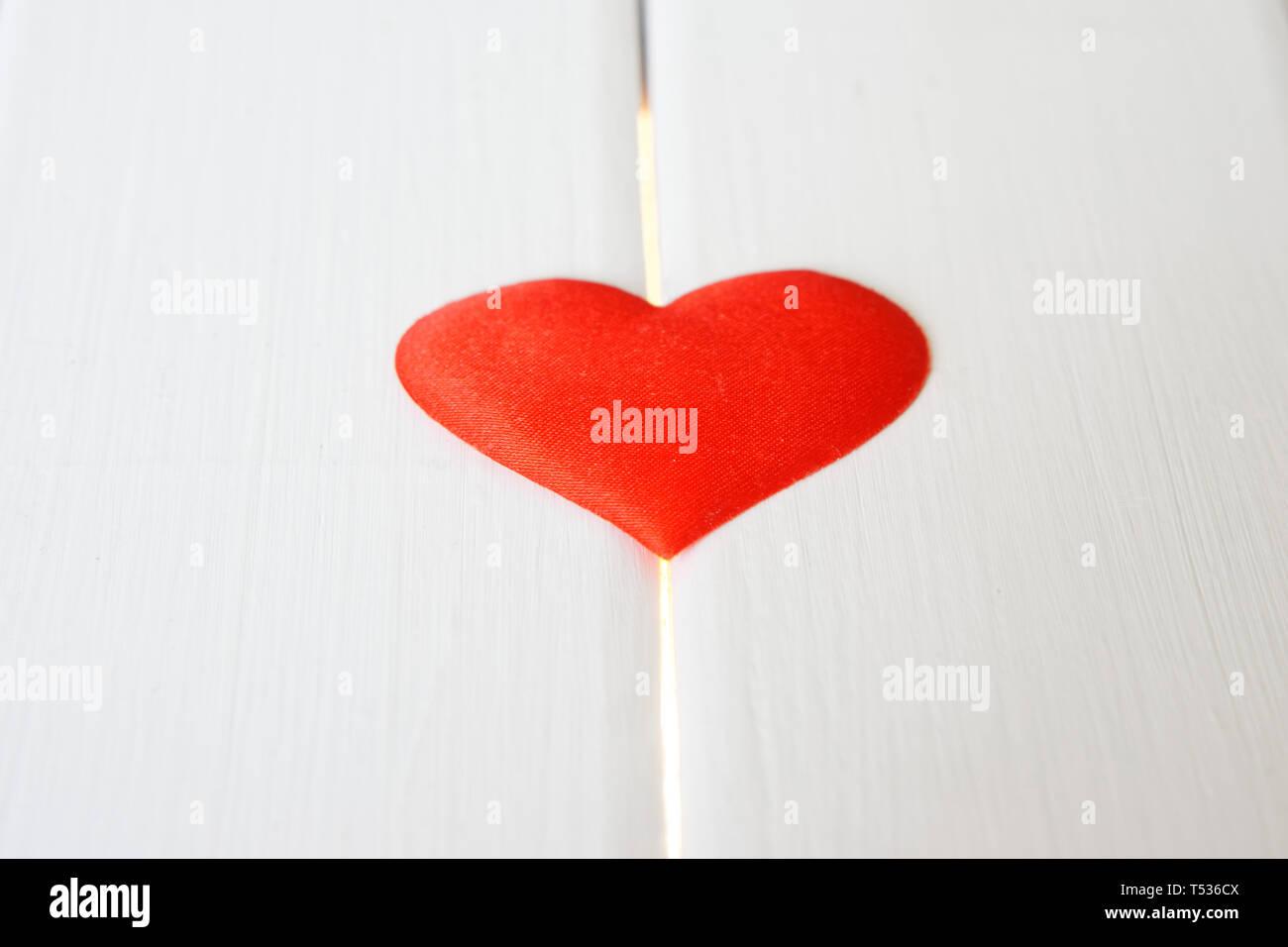 Cuore rosso su bianco di una superficie di legno e linee incandescente. Problemi di salute e di cardiologia. Preparazione di congratulazioni per il giorno di San Valentino. Foto Stock