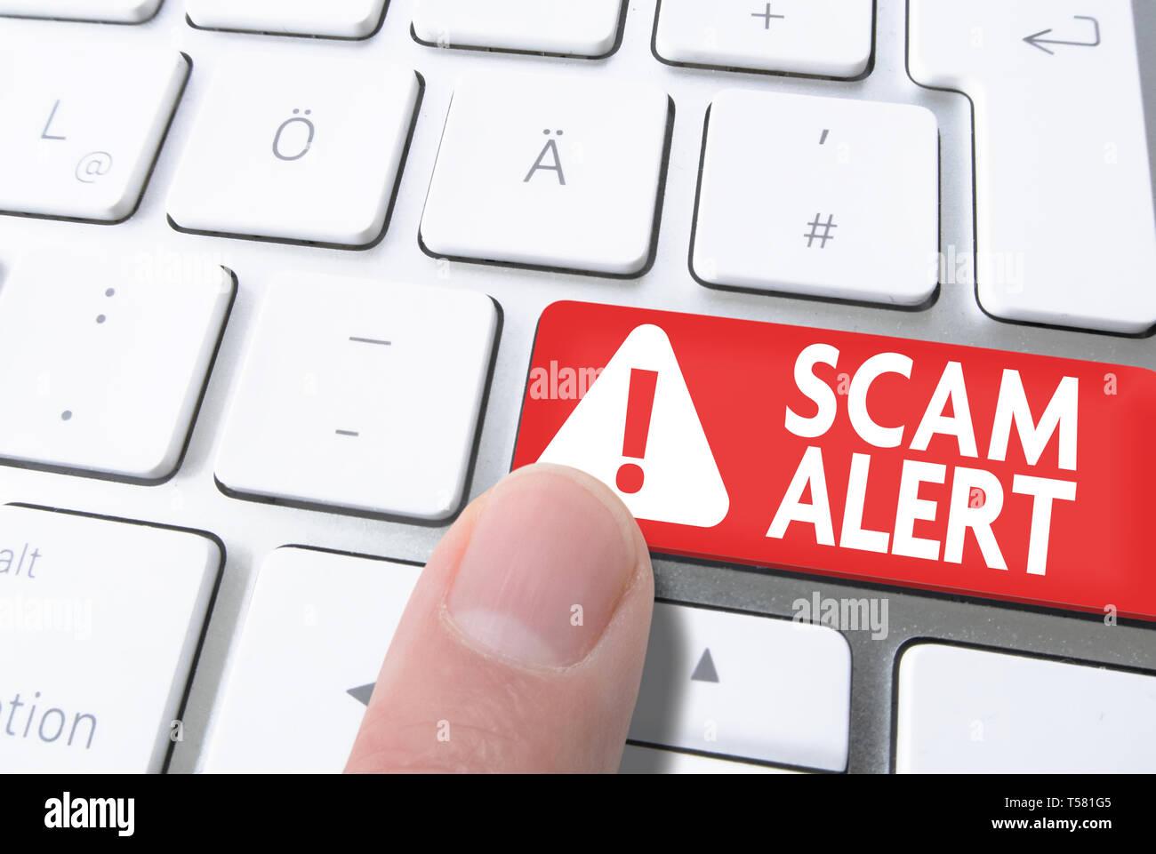 Close-up del dito che preme il tasto rosso etichettato Scam Alert sulla tastiera del computer Immagini Stock
