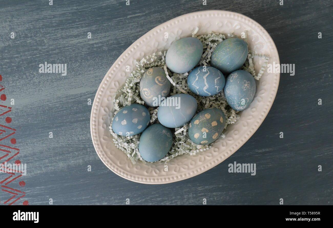 Dipinto di uova di Pasqua, colorato con un colorante dal cavolo rosso, su un gesso dipinto di blu distressed tavolo in legno Immagini Stock