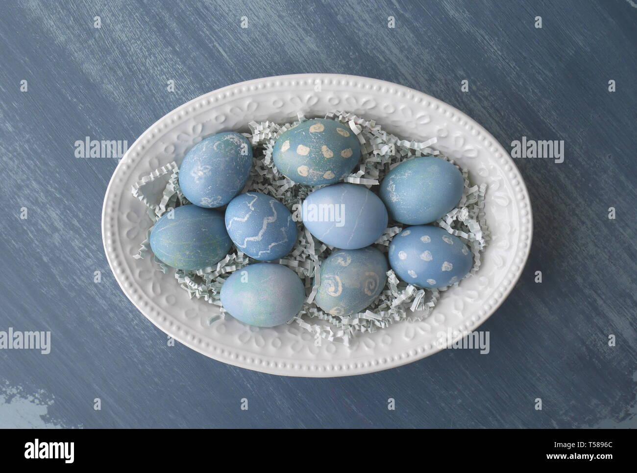 Dipinto di uova di Pasqua, colorato con un colorante dal cavolo rosso, su un gesso dipinto di blu di legno invecchiato tavolo da cucina Immagini Stock