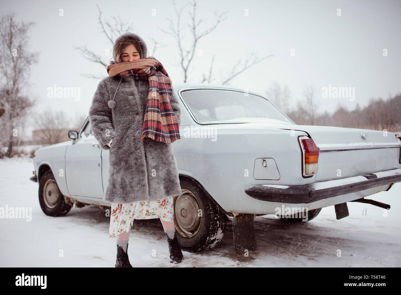 Inverno donna sorge nei pressi della macchina Foto Stock