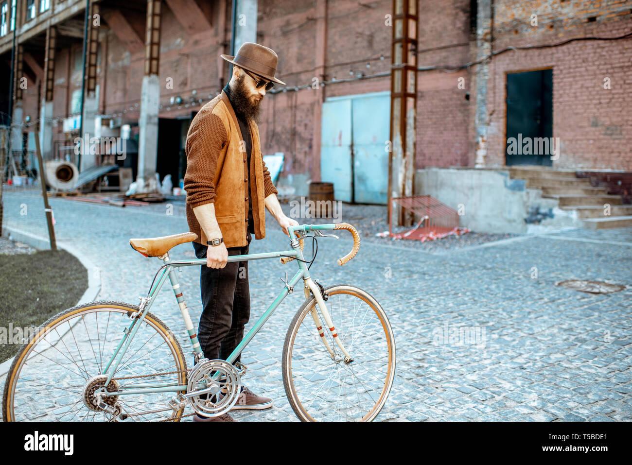 Stile di vita ritratto di un barbuto hipster vestito elegantemente camminando con retro bicicletta sul industriale di background urbano Foto Stock