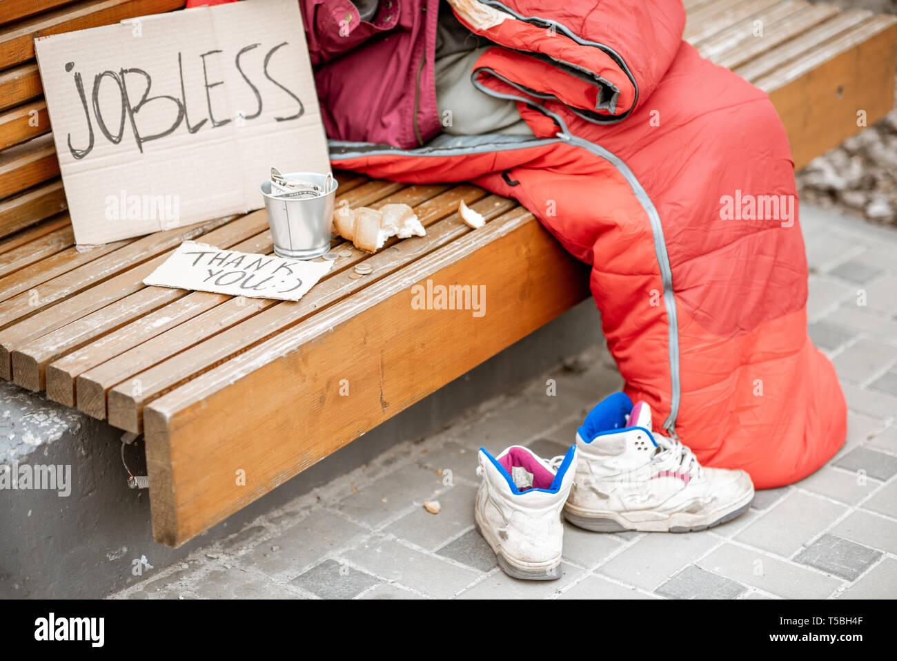Disoccupati mendicante con il cartone e la tazza di mendicare un po' di soldi e ravvicinata con nessun volto Immagini Stock