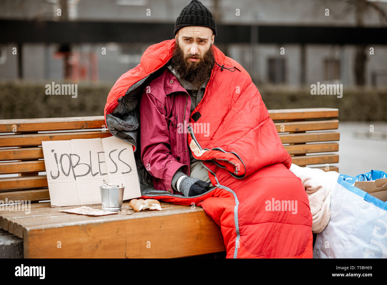 Senzatetto e disoccupati mendicante seduto sul banco avvolto con sacco a pelo di accattonaggio denaro vicino al centro business Immagini Stock