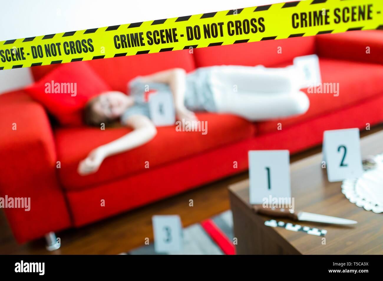 Giovane vittima in pantaloni bianchi la posa sul divano rosso - Scena del crimine con il coltello e il giallo gap non cross. Immagini Stock