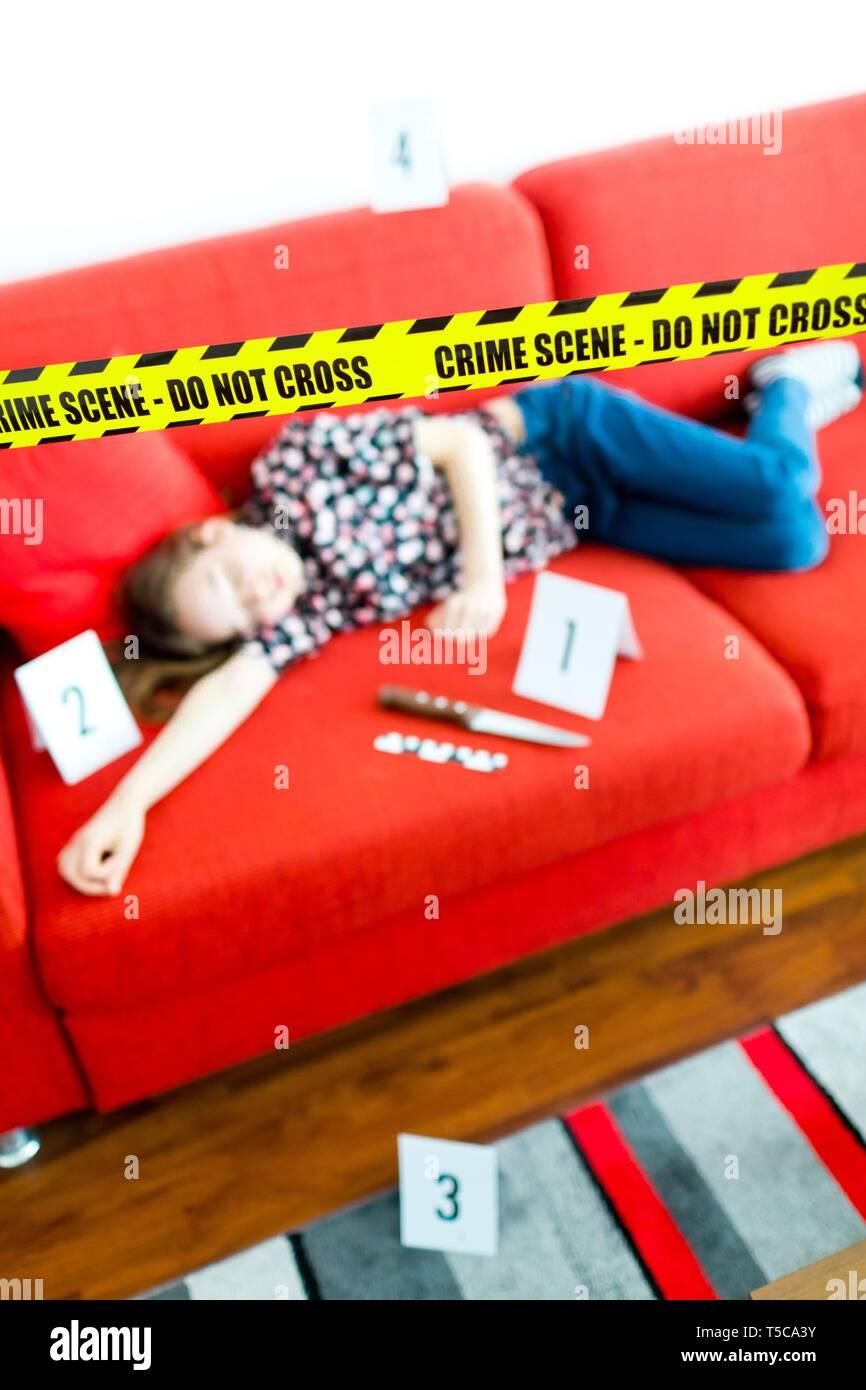Giovane vittima in jeans blu recante sul divano rosso - Scena del crimine con il coltello e il giallo gap non cross. Immagini Stock