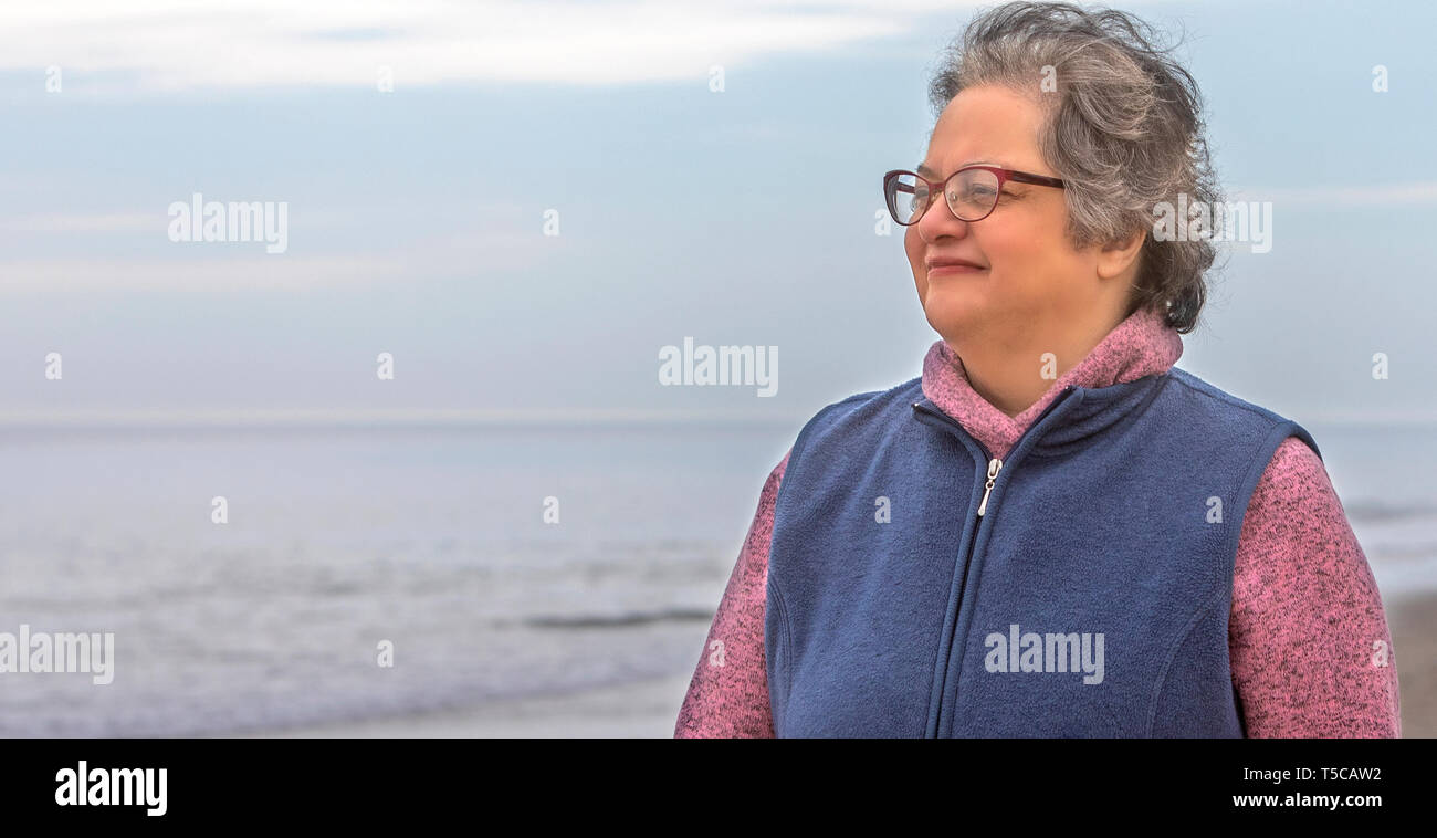 Un senior donna godendo di camminare nella sabbia sulla spiaggia dalla Ocean Shore. Immagini Stock