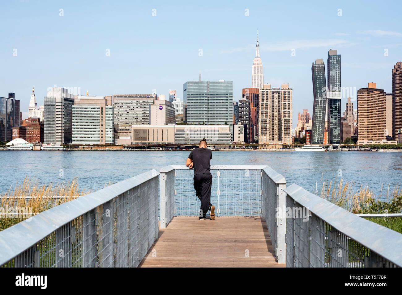 Visitatori su un ponte al di sopra di zone umide, affacciato sulla East River e Midtown Manhattan. Cacciatori South Park, New York, Stati Uniti. Architetto: Immagini Stock