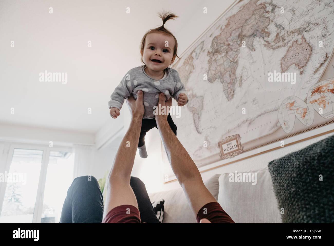 Happy Baby girl essendo sollevata da suo padre nel salotto di casa Immagini Stock