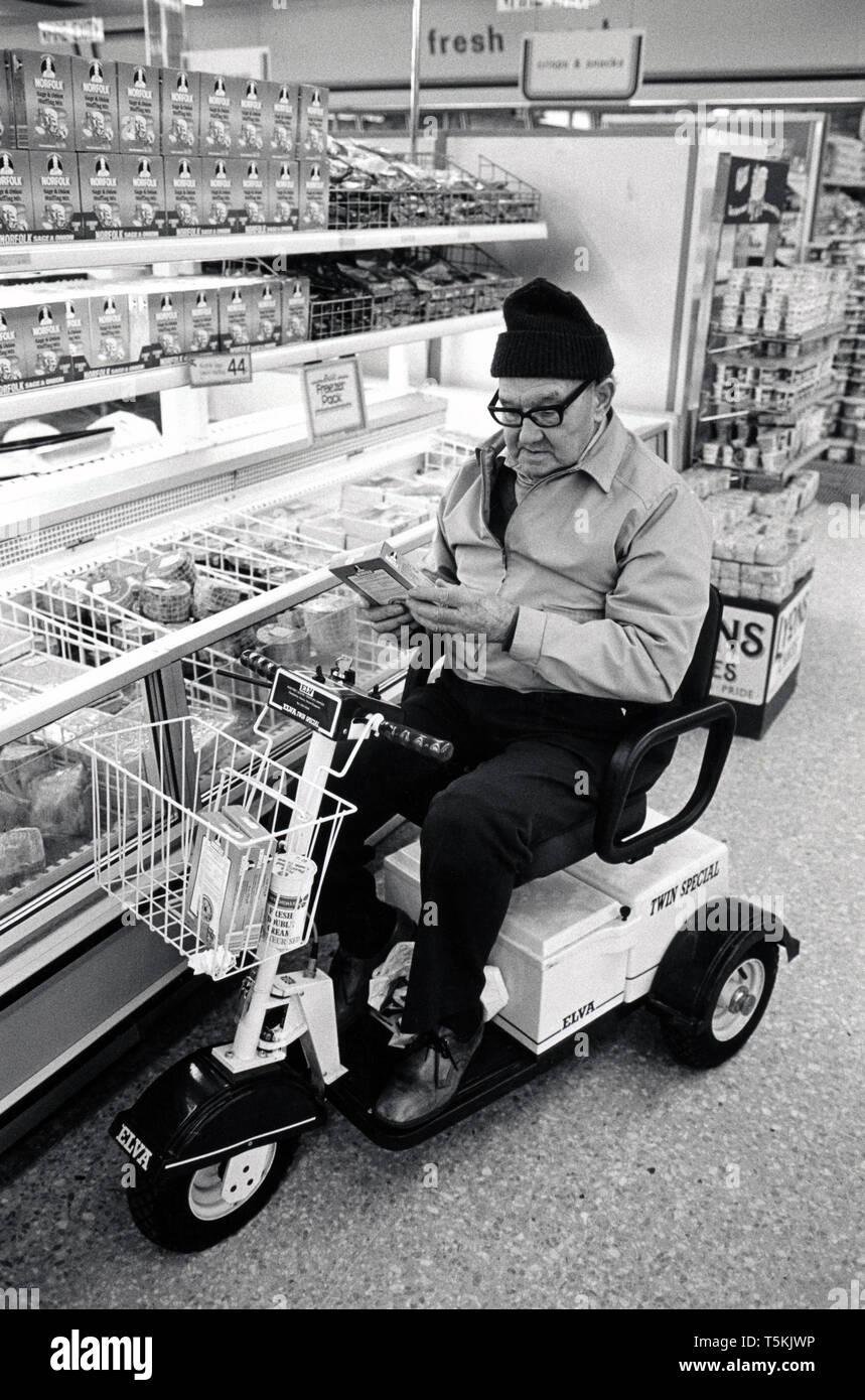 Uomo anziano in scooter di mobilità shopping nel supermercato, Regno Unito 1989 Immagini Stock